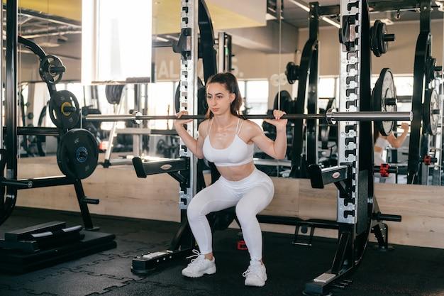 Ein junges sportliches mädchen macht übungen mit sportgeräten im fitnessstudio.
