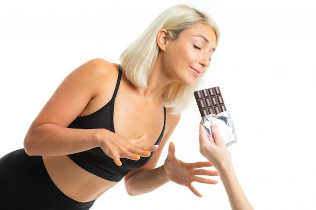 Ein junges sportmädchen mit blonden haaren betrachtet schokolade