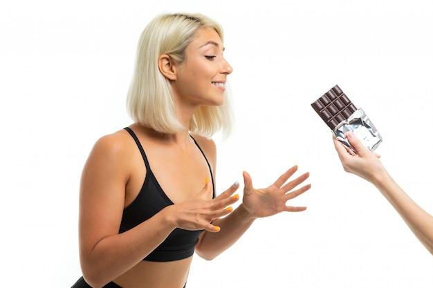 Ein junges sportmädchen mit blonden haaren in einer schwarzen sportoberseite und schwarzen gamaschen hält schokolade und möchte sie