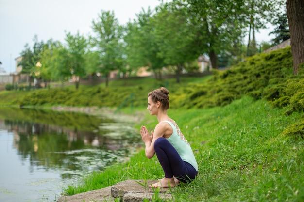 Ein junges sportmädchen übt yoga auf einem grünen rasen am fluss, yoga assans haltung. meditation und einheit mit der natur