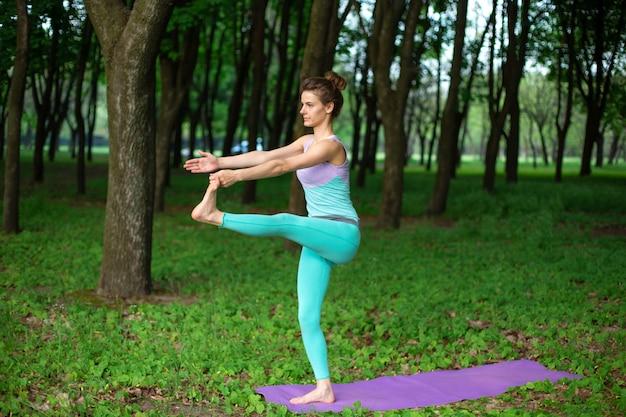 Ein junges sportmädchen übt yoga in einem beendigten grünen sommerwald, yoga assans lage. meditation und einheit mit der natur