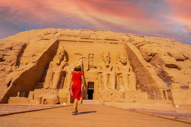 Ein junges touristenmädchen im roten kleid, das in richtung des abu-simbel-tempels in südägypten in nubien neben nasser see bei sonnenuntergang geht. tempel des pharao ramses ii