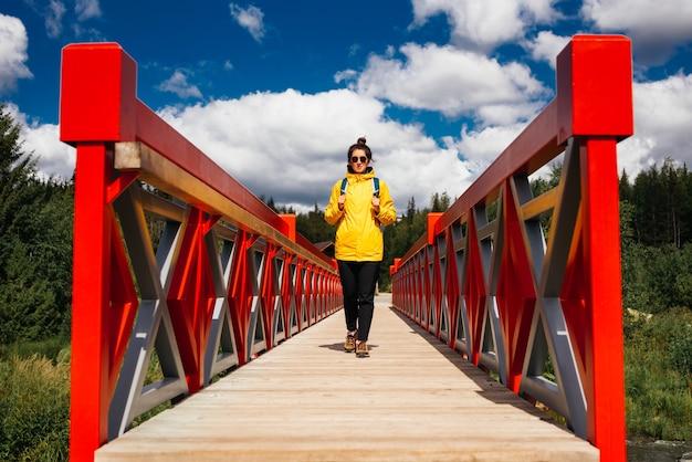 Ein junges touristenmädchen in einer gelben jacke mit rucksack geht die rote brücke entlang. ein tourist geht durch den nationalpark. ein tourist passiert den fluss durch die brücke. platz kopieren