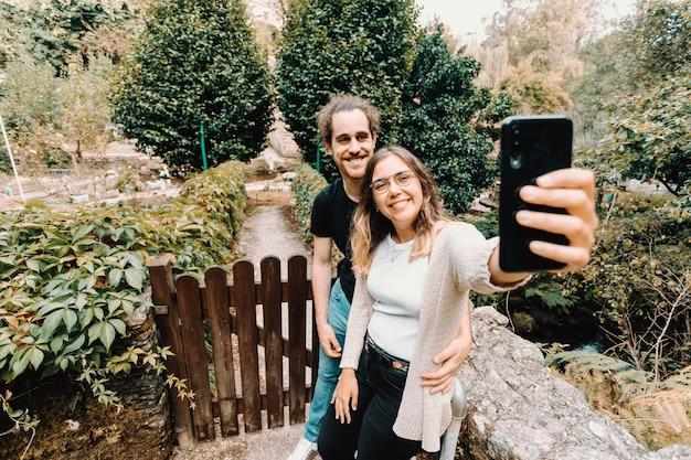 Ein junges und lächelndes paar, das ein selfie vor einem schönen ländlichen haus macht