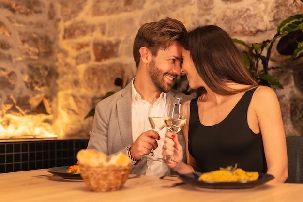 Ein junges verliebtes europäisches paar, das in einem schönen restaurant zu abend isst und valentinstag feiert