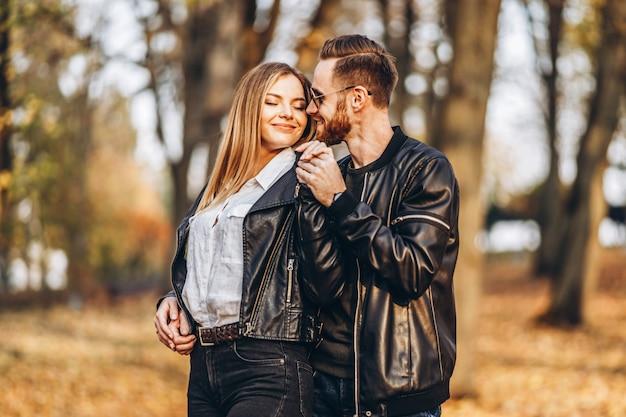 Ein junges verliebtes paar, das an einem sonnigen tag im herbstpark spazieren geht