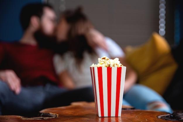 Ein junges verliebtes paar, das nachts fernsieht, romantische verabredungsnacht, die auf der couch liegt und popcorn isst