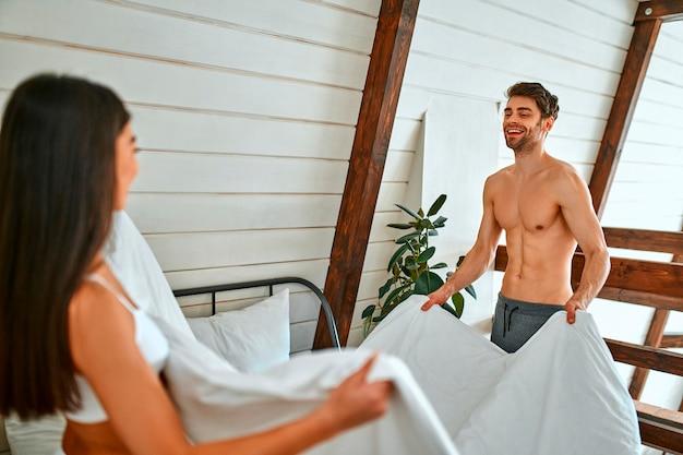 Ein junges verliebtes paar macht ein bett in einem hellen, modernen schlafzimmer. die morgenroutine des paares.