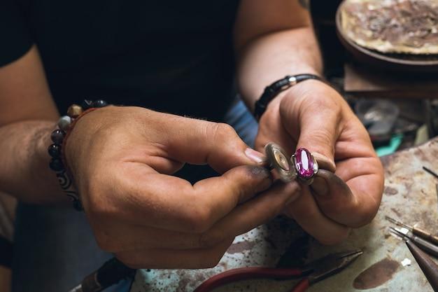 Ein juwelier reinigt einen goldring mit einem stein mit einem spezialwerkzeug in einer werkstatt, nahaufnahme