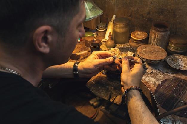 Ein juwelier repariert in seiner werkstatt einen goldring mit einem stein
