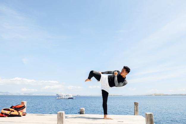 Ein kämpfender mann in einer kampfsport-kick-pose mit dem meer im hintergrund