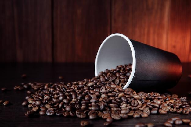 Ein kaffee-pappbecher mit kaffeebohnen auf holzoberfläche