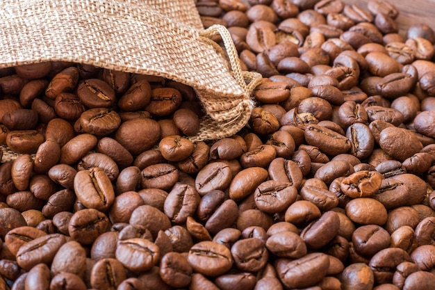 Ein kaffeebohnenhintergrund, der aus einem leinensack herausgießt
