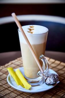 Ein kaffeegetränk in einem glas mit keksen.