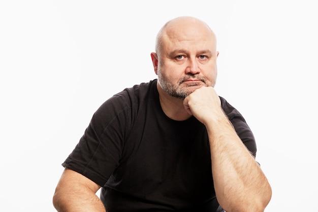 Ein kahlköpfiger mann in einem schwarzen t-shirt sitzt mit dem kopf in der hand und schaut in die kamera. weiße wand.