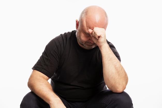 Ein kahlköpfiger mann in einem schwarzen t-shirt sitzt mit dem kopf in der hand. weiße wand.