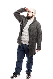 Ein kahlköpfiger mann mit brille schaut in die ferne. vollständige höhe. über weißer wand isoliert. vertikale.