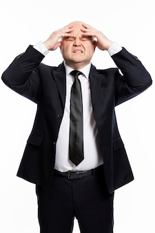 Ein kahlköpfiger mann mittleren alters in einem strengen schwarzen anzug hält sich mit den händen den kopf. geschäftsprobleme. weißer hintergrund. vertikal.