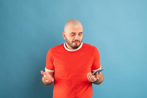 Ein kahlköpfiger mann mittleren alters mit bart und rotem t-shirt an einer blauen wand. hält ein telefon in der hand und zeigt mit dem finger seiner anderen hand darauf