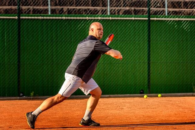 Ein kahlköpfiger mann mittleren alters spielt tennis auf dem platz im freien. sonniger tag