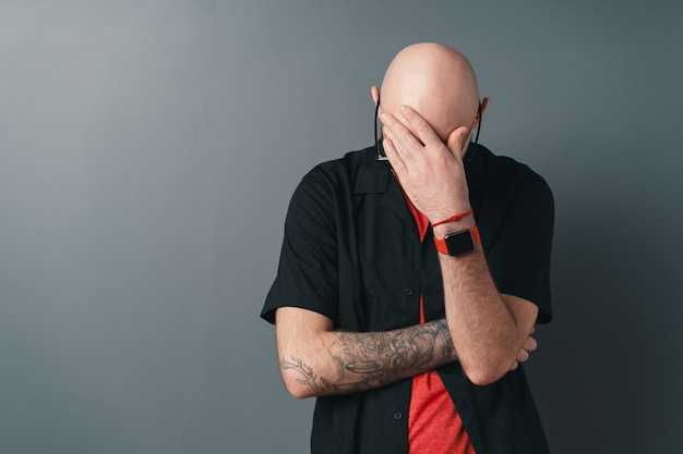 Ein kahlköpfiger, stilvoller mann, der auf grau posiert und probleme vorwegnimmt, während er stirn mit der hand berührt.