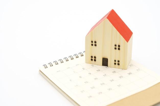 Ein kalender des monats mit modellhausmodell. verwendung als hintergrundgeschäftskonzept