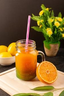 Ein kalter cocktail der vorderansicht, der in glasdosen mit bunten grünen blättern der strohzitronen auf dem hölzernen cremefarbenen schreibtisch und dunkel gefärbt wird