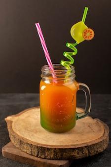 Ein kalter cocktail der vorderansicht, der innerhalb der glasdose mit buntem stroh gefärbt wird, isoliert auf dem hölzernen schreibtisch und dunkel