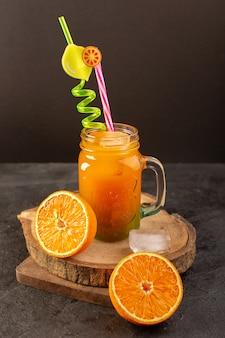 Ein kalter cocktail der vorderansicht, der innerhalb der glasdose mit buntem strohhalm mit eiswürfelorangen gefärbt wird, lokalisiert auf dem hölzernen schreibtisch und dunkel