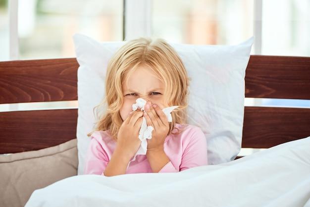 Ein kaltes porträt eines kranken kleinen mädchens mit laufender nase fangen, das an erkältung leidet oder