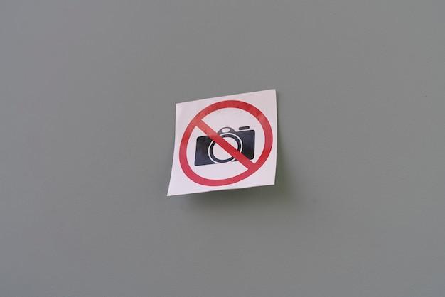 Ein kameraverbotener symbolsymbolaufkleber an der wand an einem öffentlichen ort, schießverbotsbereich