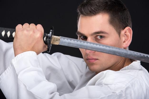 Ein kampfkunstmann im kimono mit einem schwert.