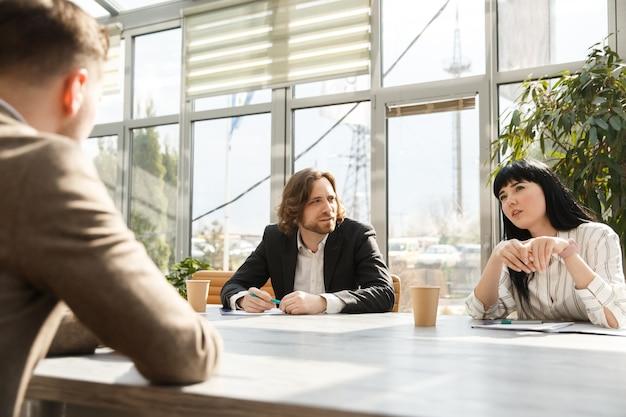 Ein kandidat spricht mit arbeitgebern über ein vorstellungsgespräch