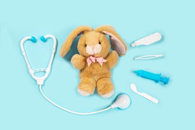 Ein kaninchen heilen. spielzeug medizinische geräte auf einem blauen hintergrund.