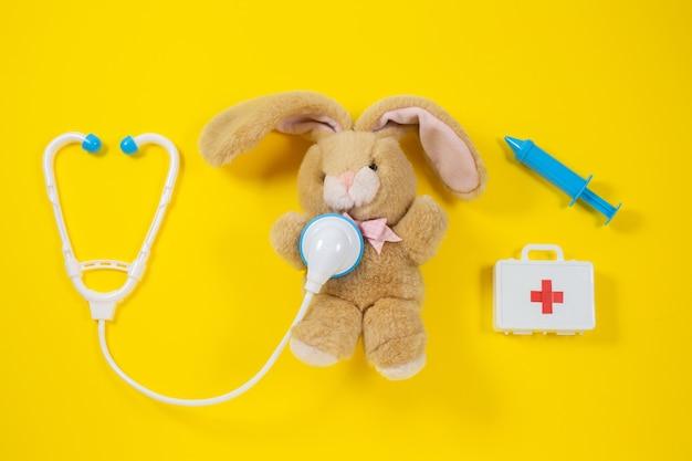 Ein kaninchen heilen. spielzeug medizinische geräte auf einem gelben.