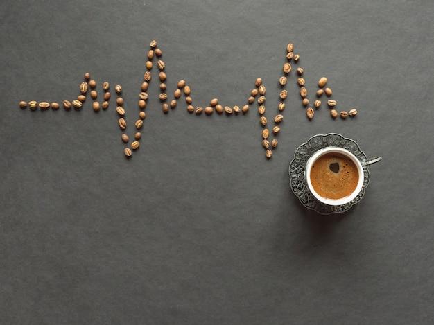 Ein kardiogramm von kaffeebohnen und eine tasse kaffee auf einem schwarzen hintergrund.