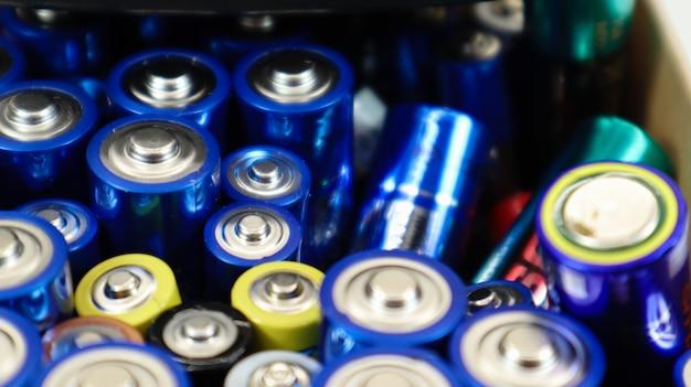 Ein karton auf weißem hintergrund voller gebrauchter aa-, aaa-alkalibatterien, die zum recycling gesammelt wurden. recycling und ökologische probleme.