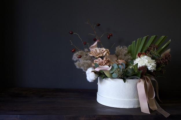 Ein kasten mit einem weinleseblumenstrauß auf einem dunklen hintergrund