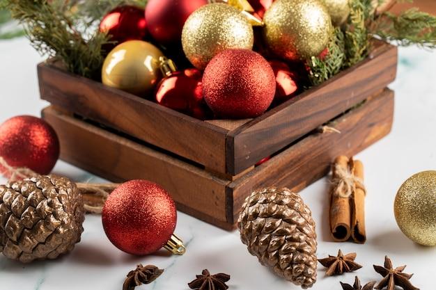 Ein kasten rote und goldene weihnachtsbaumschmucke auf dem tisch.