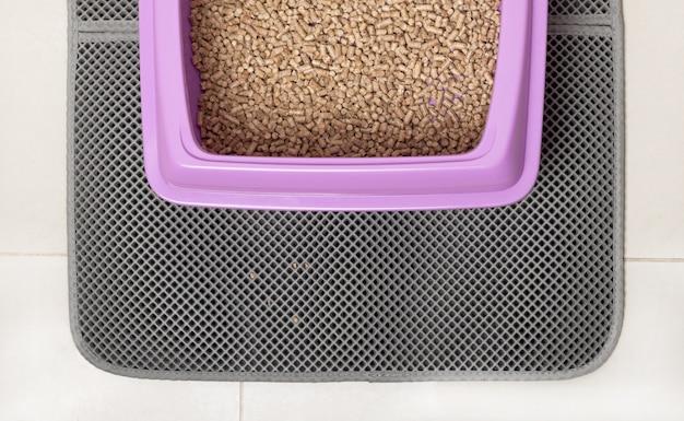 Ein katzentablett für eine toilette mit ökologischem holzfüller auf einer wasserdichten matte.