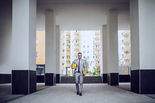 Ein kaukasischer geschäftsmann in seinem grauen anzug kommt mit seinem gelben schutzhelm und einem aktenordner in den händen auf einer baustelle an