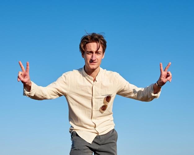 Ein kaukasischer mann aus spanien, der friedenszeichen mit beiden händen auf klarem himmel macht