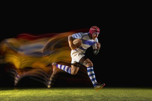 Ein kaukasischer mann, der bei gemischtem licht im stadion rugby spielt. fit junger männlicher spieler in bewegung oder aktion während des sportspiels. konzept der bewegung, sport, gesunder lebensstil.
