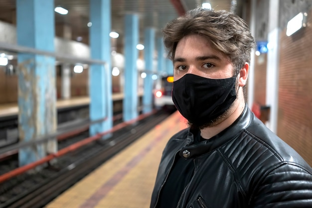 Ein kaukasischer mann mit bart in der schwarzen medizinischen maske, die in der kamera in der u-bahn schaut