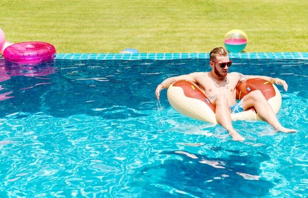 Ein kaukasischer tätowierter mann auf einem aufblasbaren floss im swimmingpool