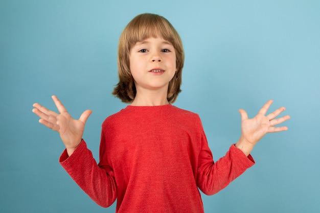 Ein kaukasischer teenager in einem roten jaket hat gereiztes, auf blauer oberfläche isoliertes bild