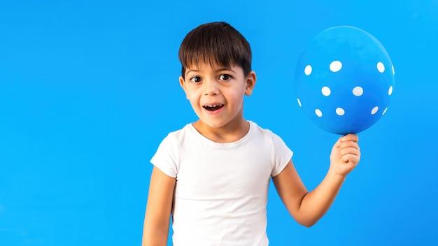 Ein kaukasisches kind freut sich über einen ballon mit weißen kreisen