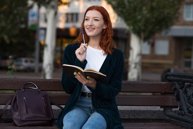 Ein kaukasisches mädchen der jungen und attraktiven rothaarigen, das auf einer bank sitzt, einen notizblock anhält und denkt.