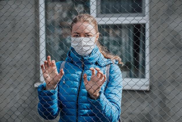 Ein kaukasisches mädchen in einer medizinischen schutzmaske steht hinter einem metallzaun und sieht traurig aus. strenge hausisolation während der quarantäne.