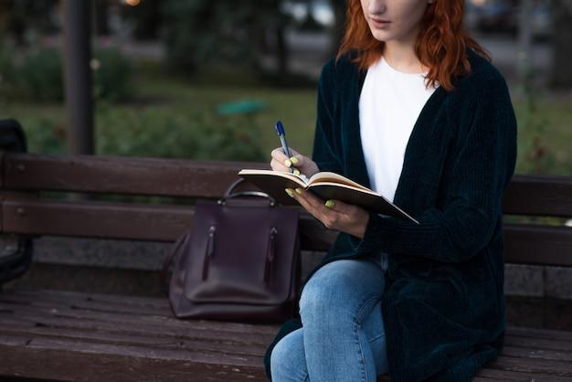 Ein kaukasisches mädchenschreiben der jungen und attraktiven rothaarigen in einem notizbuch beim sitzen auf einer bank. bildungskonzept.